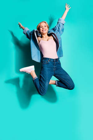 Vertical full length body size profile side view of nice attractive careless carefree cheerful sporty slim fit slender girl having fun isolated on bright vivid shine blue green turquoise background Standard-Bild