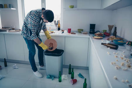 Full length body size view of nice attractive focused guy wearing checked shirt doing making perfect domestic service cleanup in modern light white interior style kitchen