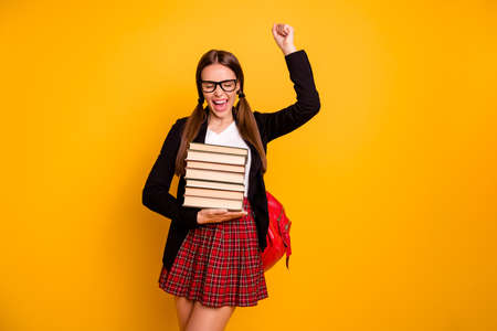Portrait tails thrilled lady teenager eyewear eyeglasses aims good marks courses raise fist scream yeah close eyes red checked plaid pullover sweater skirt black jacket isolated yellow background