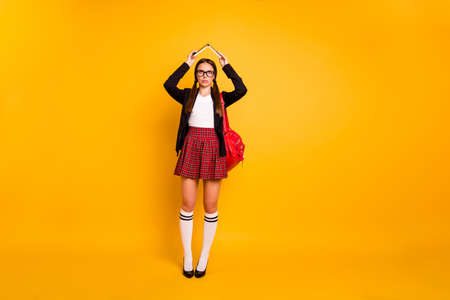 Full length body size view of nice attractive bored girl holding in hands book over head like roof boring classes courses pass exam test isolated over bright vivid shine yellow background