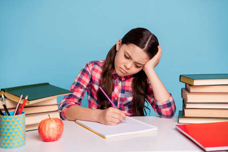 Portrait of nice attractive sad irritated annoyed clever smart girl wearing checked shirt writing diary boring home work isolated over bright vivid shine blue turquoise background Stock fotó