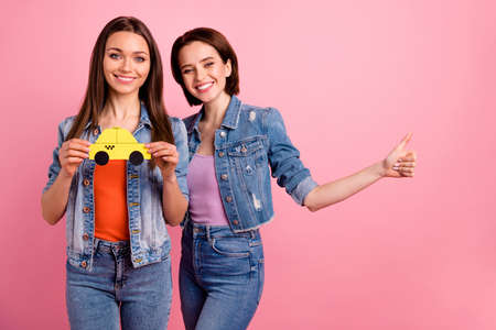Close up photo two beautiful she her sisters ladies buddies hands arms paper advert yellow taxi users thumb up symbol tips advising wear jeans denim jackets blazers isolated bright pink background