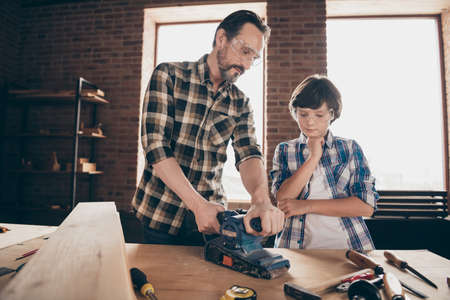 Portrait of two nice person concentrated focused woodworkers master artisan handyman dad daddy teaching son old-fashioned occupation at modern loft industrial brick interior