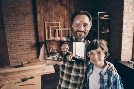 Portrait charming nice pretty lovely dad papa kid glasses goggles protective builder craftsman artisan hold hand blog blogger cabinetry sue user modern technology beard brunet hair home plaid shirt Stock Photo - 127748160