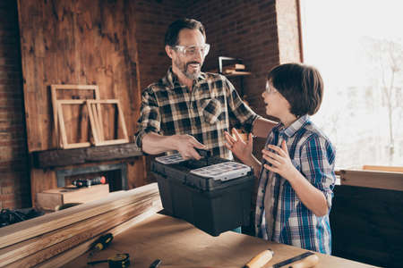 Portrait of two nice person cheerful cheery glad woodworkers master handyman dad giving new cool toolbox toolkit to son production at modern loft industrial brick interior Stock fotó