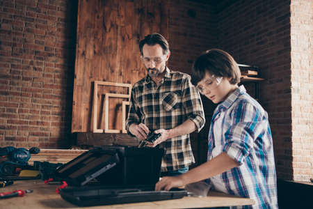Portrait successful craftsmen occupation hobby fix hardwood touch tools helper support son kid glasses master explain beard checkered shirt trendy stylish modern indoors glasses goggles protective
