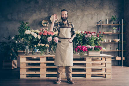 Full length body size view of his he nice attractive cheerful content guy wearing uniform among peony different bunch sales manager showing ok-sign at industrial concrete style salon indoors