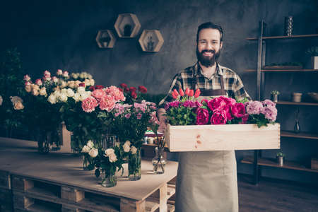 Portrait of his he nice attractive cheery cheerful content successful guy professional gardener holding big box peony tulip at industrial loft concrete style indoors