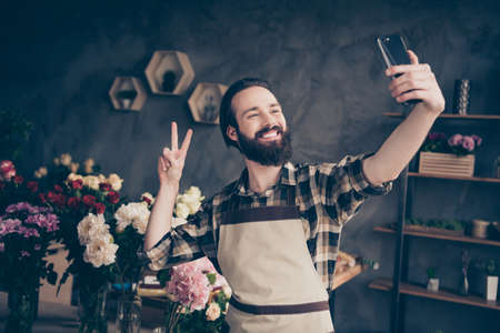 Portrait of charming attractive sweet self-employed people entrepreneur person hold hand modern technology camera content enjoy rest free time occupation hobby make v-sign wear checked shirt