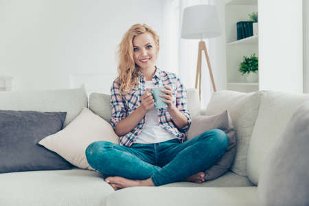Portrait of her she nice-looking attractive lovely lovable adorable shine cheerful cheery healthy wavy-haired girl in checked shirt sitting on divan having espresso at white light style interior Stockfoto