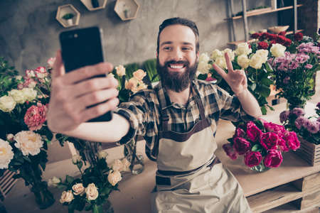 Portrait of his he nice attractive cheerful cheery glad funny positive guy gardener making taking selfie showing v-sign enjoying at modern industrial loft concrete style salon indoors Stock fotó