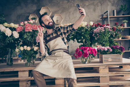 Portrait of his he nice attractive cheerful cheery positive guy gardener sitting making selfie showing v-sign at modern industrial loft concrete style salon indoors