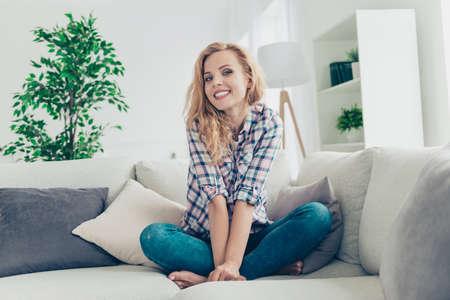 Ritratto di lei lei bella attraente bella dolce amabile modesta lucentezza allegra ragazza dai capelli ondulati allegra in camicia a quadri che si siede sul divano divertendosi al soggiorno interno in stile luce bianca
