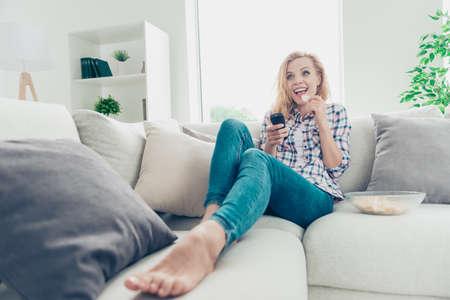 Lage hoekmening van haar, ze ziet er leuk uit, mooi, charmant, schattig, vrolijk, blij, golvend meisje in geruit hemd, liggend op een divan en kijkend naar een komiek in een witte lichte stijl interieur woonkamer