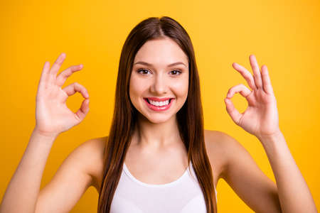 Close up photo beautiful amazing she her lady positive good job hands arms okey symbol agreement advise low price buy buyer quality product wear casual white tank-top isolated bright yellow background