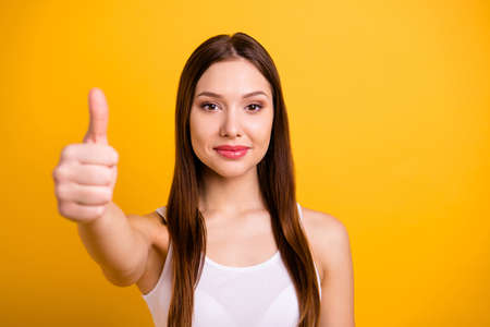 Close up photo beautiful amazing she her lady perfect appearance hand arm thumb up symbol agreement advise low price buy buyer product wear casual white tank-top isolated bright yellow background