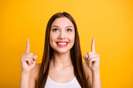 Close up photo beautiful funny she her lady perfect appearance hands arms index fingers indicate look up empty space advising buy buyer wear casual white tank-top isolated bright yellow background