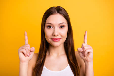 Close up photo beautiful funny she her lady ideal perfect appearance hands arms index fingers indicate up empty space advising buy buyer wear casual white tank-top isolated bright yellow background