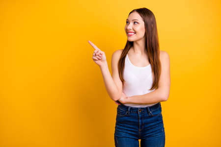 Close up photo beautiful she her lady perfect appearance hand arm index finger indicate empty space news advising buy buyer wear casual jeans denim white tank-top isolated bright yellow background Stock Photo