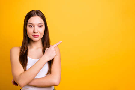 Close up photo beautiful amazing she her lady ideal perfect appearance hand arm index finger indicate empty space advising buy buyer wear casual white tank-top isolated bright yellow background