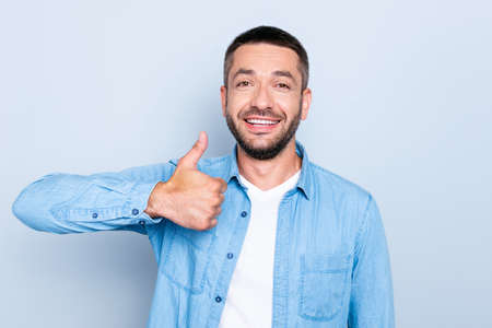 Close up photo amazing he him his guy macho perfect appearance white teeth hand arm raised up thumb up symbol advising good new product wear casual jeans denim shirt isolated grey background