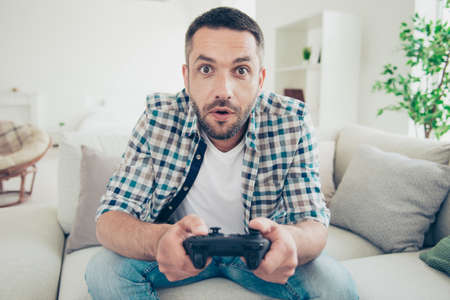 Close up photo of focused handsome mature guy hold hand have play station game pad dressed plaid denim jeans sit divan bearded amazed big apartment Stock Photo - 127878146
