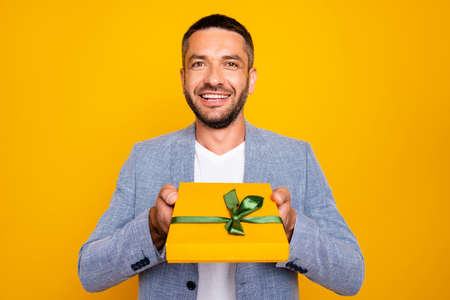 Close-up portrait of his he nice-looking attractive cheerful cheery guy wearing grey blazer holding in hands giving you good romantic purchase gift isolated over bright vivid shine yellow background Standard-Bild