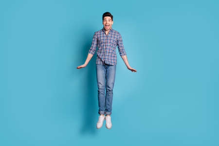 Full length body size view photo of positive cheerful careless guy laugh shout feel satisfied content candid wear modern youth outfit legs denim sneakers isolated on blue background Stock Photo