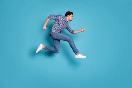 Full length body size view of concentrated athlete coach trainer do workout dressed fashionable outfit checked shirt denim sneakers isolated on blue background 版權商用圖片