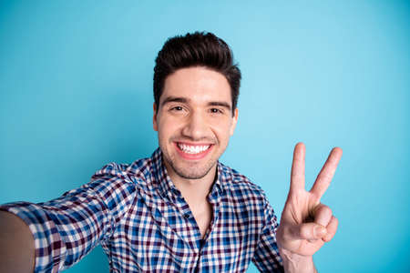 Closeup photo portrait of handsome positive cheerful he guy having free time video call making selfie give v-sign to viewers followers isolated pastel background Reklamní fotografie