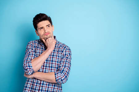 Close up photo amazing he him his macho look up empty space unsure doubtful arm touch chin think over business startup project wear casual checkered plaid shirt isolated bright blue background Banco de Imagens