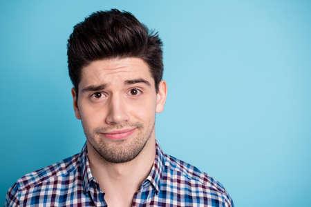 Nahaufnahme Foto von enttäuschten Kerl Millennial weiß nicht Stirnrunzeln kann keine Lösung finden Entscheidung Wahl deprimiert tragen modische Jugendkleidung einzeln auf blauem Hintergrund