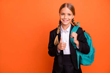 Close up photo beautiful she her little lady funky funny hairdo hand arm thumb raised up approval quality news wear formalwear shirt blazer skirt school form bag isolated bright orange background Banque d'images