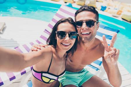 Cute pair spending honeymoon enjoying sunny day taking selfies showing v-sign symbol