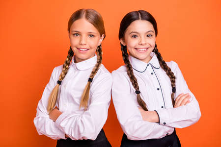 Close-up portrait of two person nice-looking attractive charming cute lovely cheerful content pre-teen girls folded arms isolated over bright vivid shine orange background Imagens