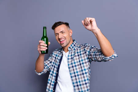 Portrait of his he nice attractive cheerful cheery careless bearded guy wearing checked shirt holding in hand light beer bachelor amusement isolated over gray blue background Stock Photo