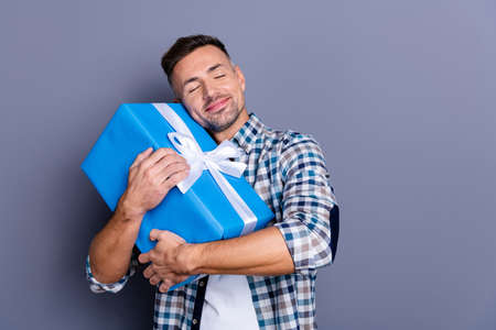 Portrait of his he nice attractive cheerful bearded guy wearing checked shirt holding in hands hugging festive celebratory box isolated over blue violet purple pastel background