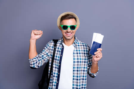 Close up photo handsome he him his guy arm hand passport tickets won lottery go free abroad foreign country funny hat bag wear sun specs casual plaid checkered shirt isolated grey background