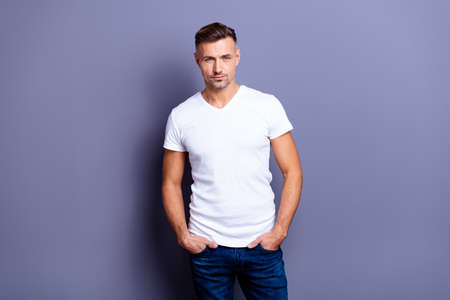 Close up photo amazing he him his middle age macho perfect appearance easy-going reliable person hands arms pockets wear casual jeans denim pants trousers white t-shirt isolated grey background