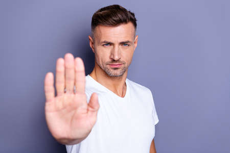 Close up photo amazing he him his middle age macho hand palm arm raised air angry look straight you will not pass through facial expression harsh wear casual white t-shirt isolated grey background