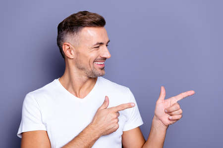 Close up photo amazing he him his middle age funny macho perfect, appearance hand arm index finger direct empty space sincere cheerful charming wear casual white t-shirt isolated grey background Stockfoto