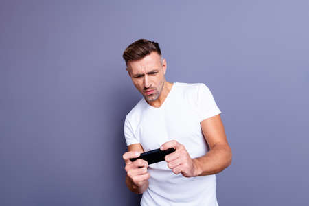 Close up photo amazing he him his middle age macho perfect appearance easy-going, telephone hands arms excited video game player trying hard wear casual white t-shirt isolated grey background