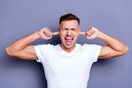 Close up photo amazing he him his middle age macho hands arms hide ears full anger outraged rage grin teeth complaining noise loud music neighbors wear casual white t-shirt isolated grey background