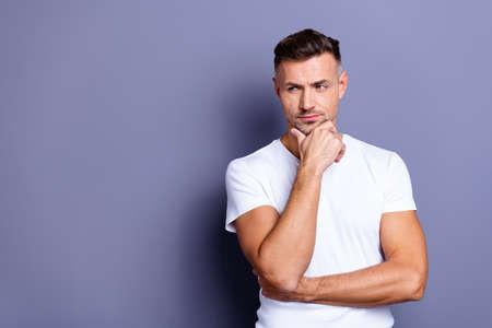 Gros plan photo incroyable il lui son âge moyen macho apparence parfaite mains bras menton regard côté espace vide pensif méditer douteux incertain incertain porter décontracté t-shirt blanc isolé fond gris