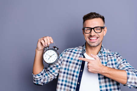 Close up photo handsome he him his guy arm hand indicating cool old-fashioned retro metal alarm excited easy awakening not miss job work wear casual plaid checkered shirt isolated grey background Stockfoto