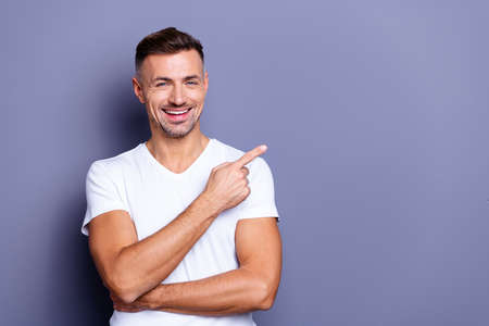 Close up photo amazing he him his middle age macho perfect appearance hand arm index finger direct empty space sincere funny cheerful charming wear casual white t-shirt isolated grey background