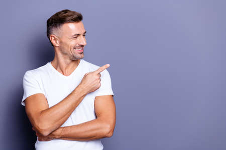 Close up photo amazing he him his middle age funny macho perfect appearance hand arm index finger direct empty space sincere cheerful charming wear casual white t-shirt isolated grey background
