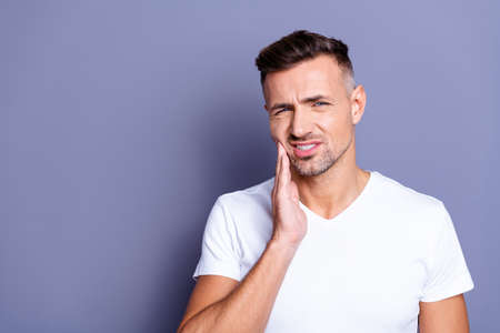 Close up photo amazing he him his middle age macho hand arm hold cheekbone teeth terrible pain injury sadness cry facial expression weakness wear casual white t-shirt isolated grey background Stock Photo