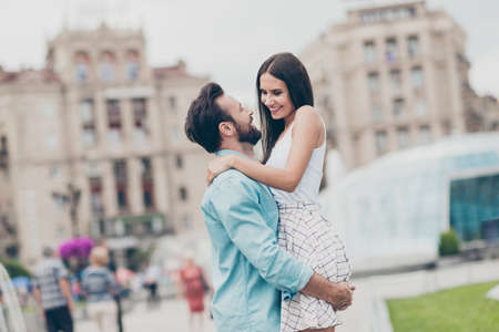 Portrait of carefree romance romantic couple have free time holidays promenade cuddling hold hand sweetheart excited bearded shirt blue denim jeans white stylish dress town outside rest relax Stock Photo