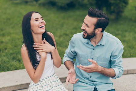 Portrait of cite charming nice pretty lady male have free time sit bench vacation laugh excited fun funny funky dressed white skirt shirt blue denim jeans close eyes touch chest bearded outside town